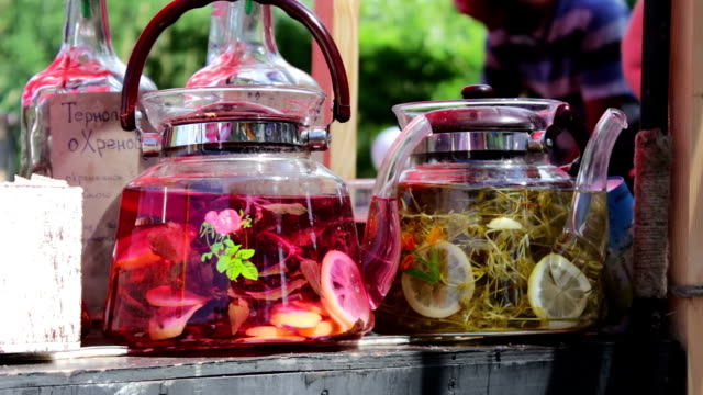 Stylish transparent beautiful teapot with herbal infusion and lemon inside. Street food. Cafe in the open air. Food fair video