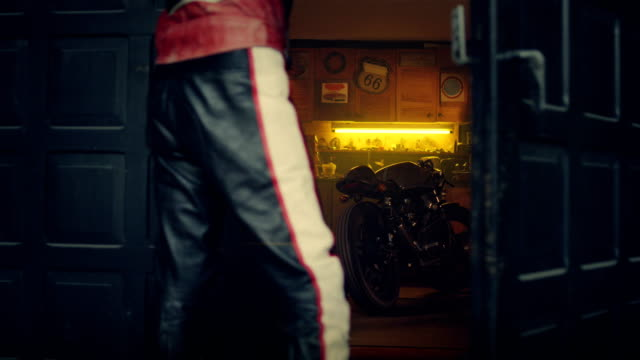 Stylish vintage hobby motorcycle garage. Man entering workshop