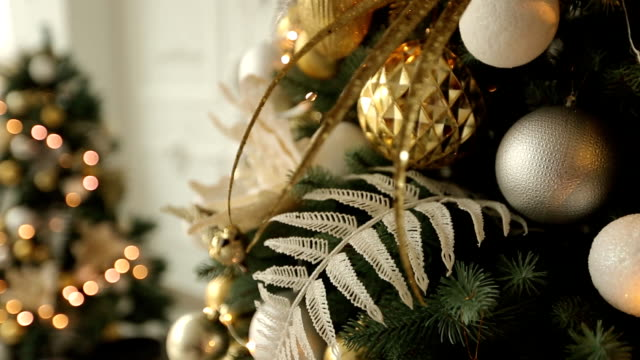 stylish white christmas interior with decorated fir trees, fireplace, lanterns, lamps, candles, wreath, bumps and gifts. comfort home with christmas tree full of golden decorations, lights and garlands. new year's eve - decorare video stock e b–roll