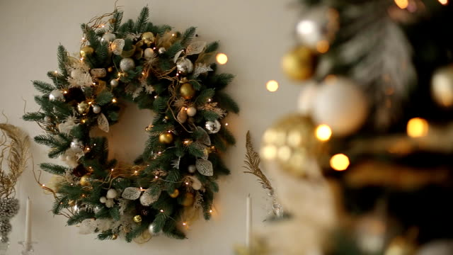 Stylish white interior with fir christmas trees, and wreath full of golden decorations, toys, lights and garlands. Wreath on background. New Year's Eve at home video