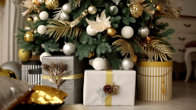 vídeos de stock e filmes b-roll de stylish white interior with handmade gifts and presents decorated with ribbons and bumps under the christmas tree. comfort warm home full of golden decorations, lights and garlands on new year's eve - living room background