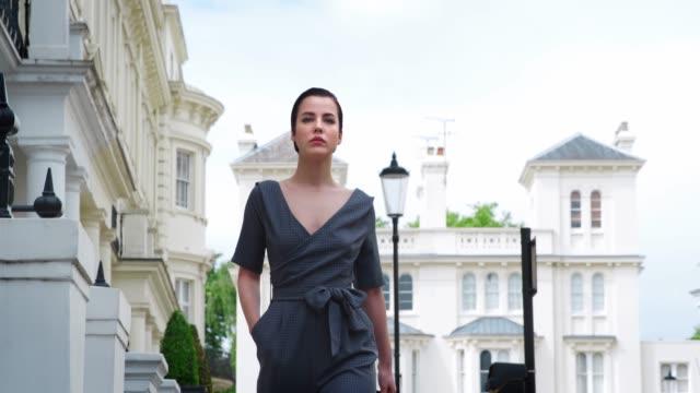 キャリング バッグ流行の女性が街を歩く ビデオ
