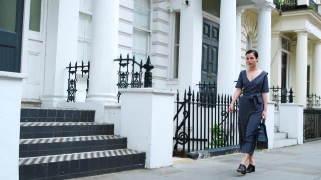 Mujer elegante bolsa de transporte paseos a lo largo de la calle de la ciudad - vídeo