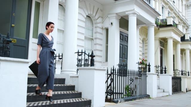 stylish woman carrying bag walks along city street - london fashion stock videos and b-roll footage