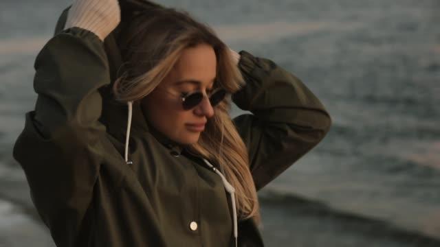 vídeos y material grabado en eventos de stock de mujer elegante en gafas de sol llevan sudadera con capucha de pie en el río - moda de otoño