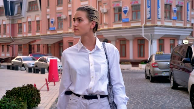 Stylish woman is walking down street and watching around in daytime, urban concept
