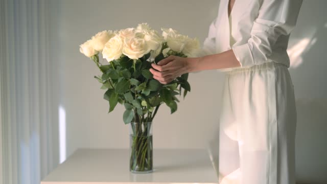 Stylish woman puttting flowers on the table