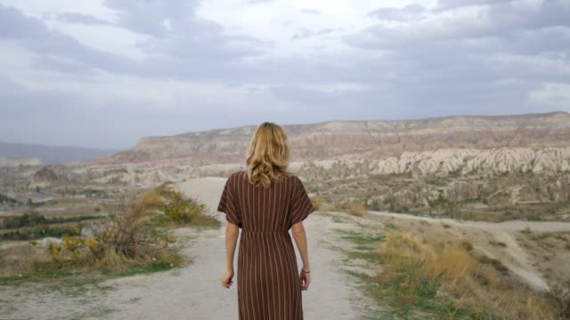stylish woman running down the valley of cappadocia