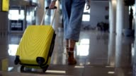 istock Stylish woman walk with trolley yellow case by empty airport, low half view of slender female legs and medium wheeled bag, smooth tracking shot. Wearing jeans and brown boots. Rare view 1217323330