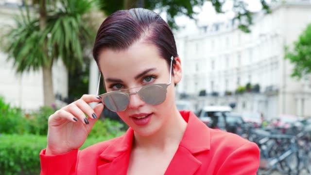 Mujer elegante que llevaba gafas de sol de pie en la calle de la ciudad - vídeo
