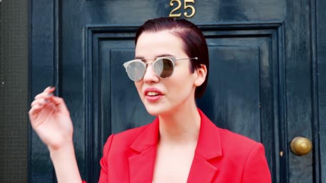 スタイリッシュな女性サングラス青いドアの外に立っています。 - スタイリッシュ点の映像素材/bロール
