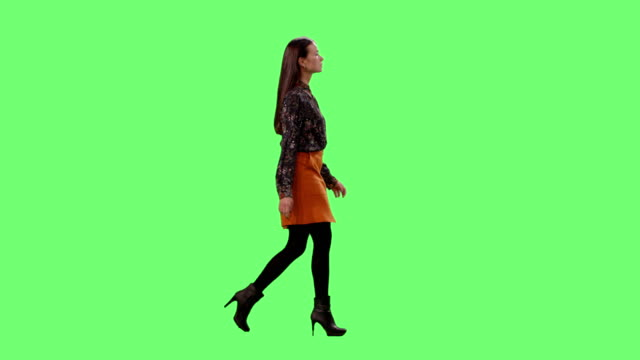 vídeos de stock e filmes b-roll de stylish young brunette gracefully walking. shot on a mock-up green screen in the background. - figura para recortar