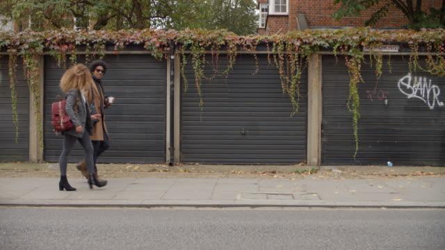 街のガレージ前を歩いスタイリッシュな若いカップル - street graffiti点の映像素材/bロール