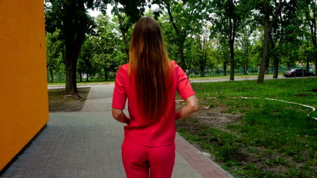 Stylish young girl in a red suit walking down the street video