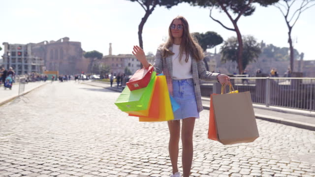 stylish young girl walking and dancing in the city centre with shopping bags after purchasing - borsa della spesa video stock e b–roll