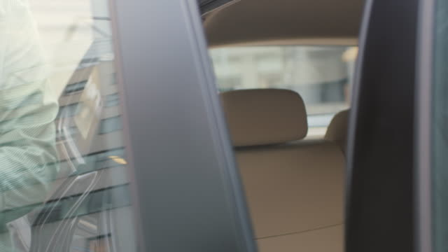 stylish young man gets into backseat of a car, fastens his seatbelt ready for a ride. - entrare video stock e b–roll
