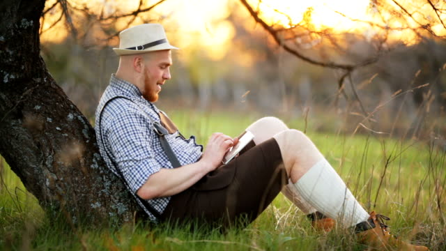 Stylish young man in the park with tablet in hands video