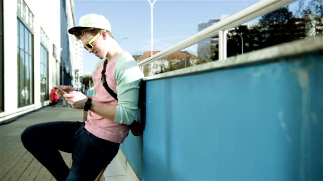Stylish young man in the street using tablet in the city. video