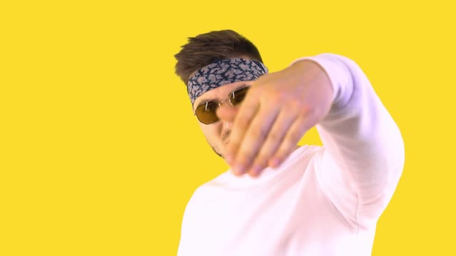 Stylish Young Man in Trendy Glasses and a Bandana stands and looks into the frame and waves his hand away. Back yellow background.