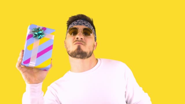 Stylish Young Man In Trendy Glasses, Bandana Holds A Gift And Dances. Back yellow background. Festive mood