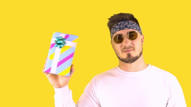 Stylish Young Man in Trendy Glasses, Bandana Shakes a Box with a Gift and Listens Inside the Box.
