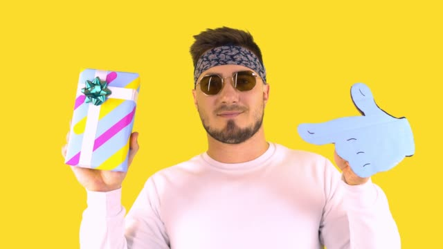 Stylish Young Man In Trendy Glasses, Bandana Shows Thumb At Box With Gift. Back yellow background. Festive mood