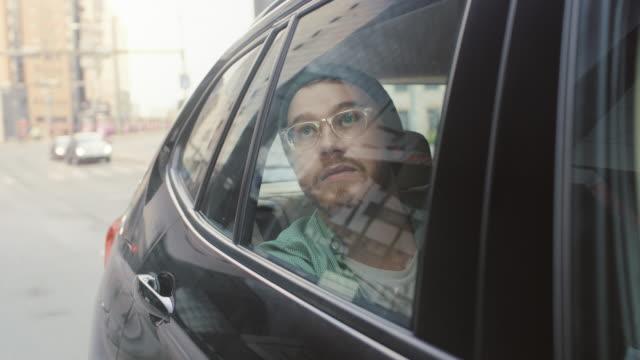 şık genç adam üzerinde bir yolcu arka koltuğunda görünüyor merak içinde belgili tanımlık pencere dışında bir araba sürmek. büyük şehir görünümü penceresinde yansıtır. kamera dışında hareketli araba monte. - hipster kişi stok videoları ve detay görüntü çekimi