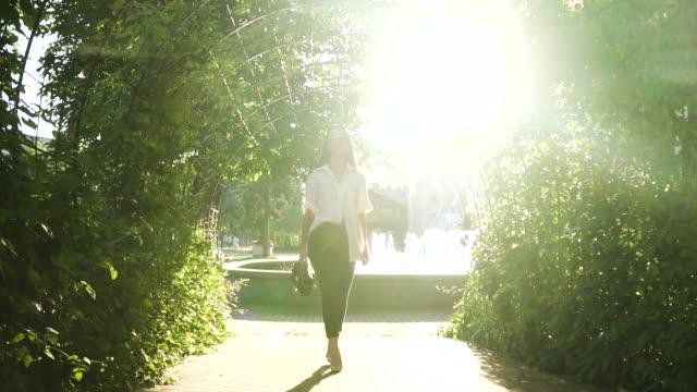 vídeos y material grabado en eventos de stock de joven elegante en tacones, caminar en el parque en el fondo de fuentes - moda de verano