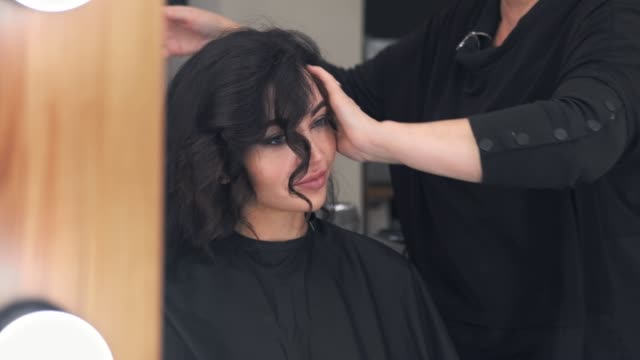 stylish young woman doing hair styling in a professional beauty salon sitting opposite the mirror