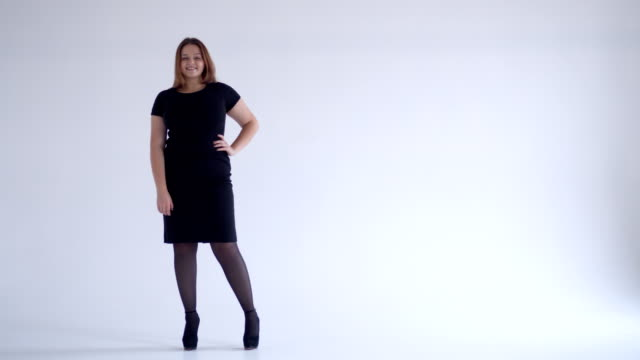 Stylish young woman in black dress looking at camera Full-length of stylish young woman in black dress looking at camera full length stock videos & royalty-free footage