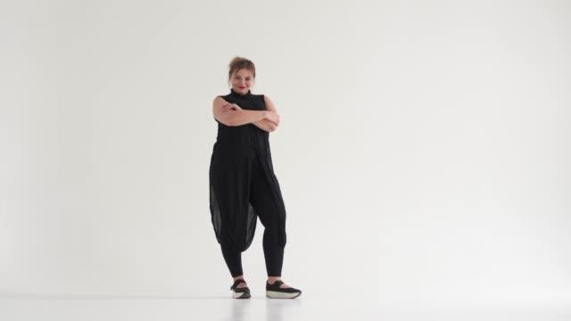 stylish young woman in black dress - mani sui fianchi video stock e b–roll