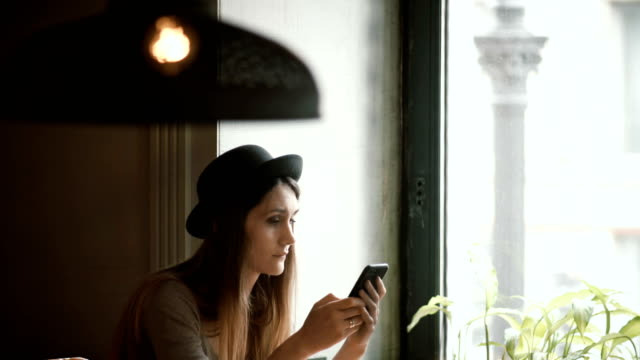 Stylish young woman in hat using the smartphone in cafe. Attractive female browsing the Internet sitting near the window video