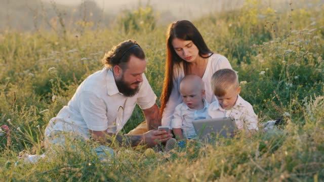 vidéos et rushes de une élégante jeune femme avec des cheveux longs avec un mari barbu et deux petits enfants cool regarder une vidéo sur une tablette - foin