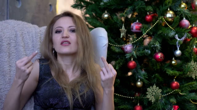 Stylish young woman with pink lipstick sitting near christmas tree and showing middle finger video