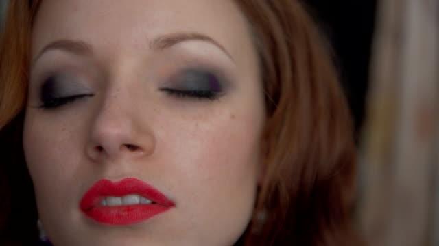 stockvideo's en b-roll-footage met stylist veroorzaakt schaduwen op het bovenste ooglid voor het model met borstel voor make-up - eyeliner