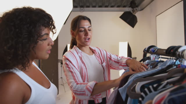 Stylist Discussing Wardrobe With Female Photographer On Fashion Shoot In Studio Stylist discussing wardrobe with female photographer on photoshoot - shot in slow motion photo shoot stock videos & royalty-free footage