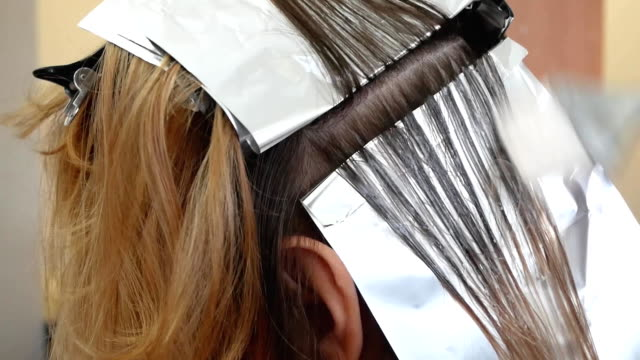 Stylist hairdresser makes hair coloring, blonding, coloring hair roots. video
