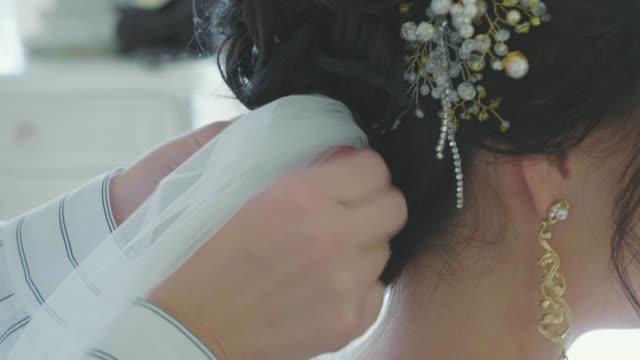 stylist inserting a veil into the brides hair before the wedding - аксессуар для волос стоковые видео и кадры b-roll