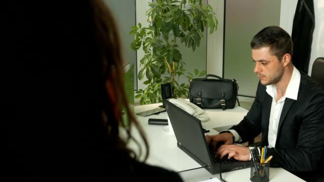 vídeos de stock, filmes e b-roll de subjectiva vista traseira foto de uma mulher assistindo um homem trabalha em um computador portátil no escritório - primeira comunhão