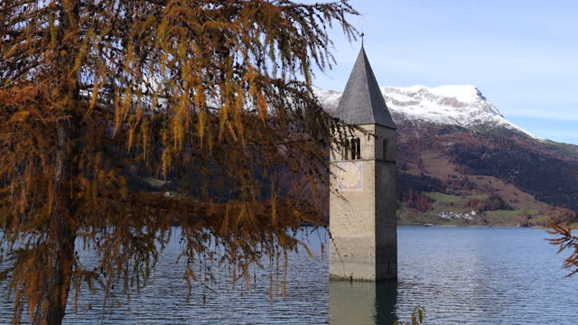 Submerged church and steeple in a lake Spooky submerged bell tower sticking out from a lake in Curon Venosta, Italy. Famous touristic destination. Autumn fall foliage pine or birch in foregund. charming stock videos & royalty-free footage