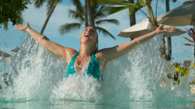 SLOW MOTION: Submerged tourist outstretches her arms and stands up out of water. video