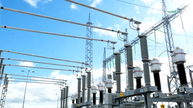 substation converts electrical energy under sunlight - sottostazione elettrica video stock e b–roll