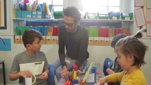 un tutor sostitutivo che aiuta in una lezione - arti e mestieri video stock e b–roll