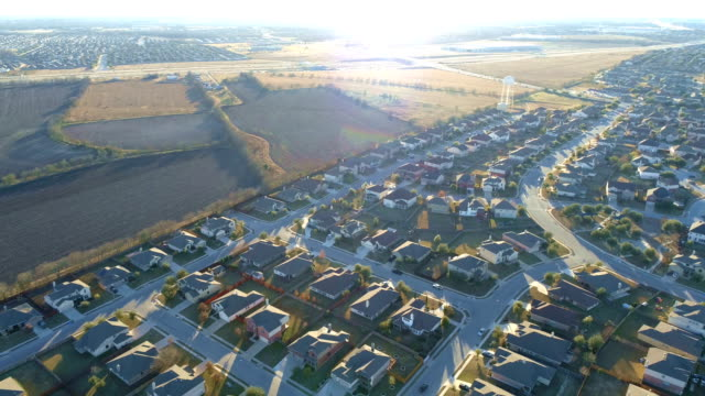 suburb neighborhood with sunflare or lens flare effect at sunset with thousands of homes from drone view - città diffusa video stock e b–roll
