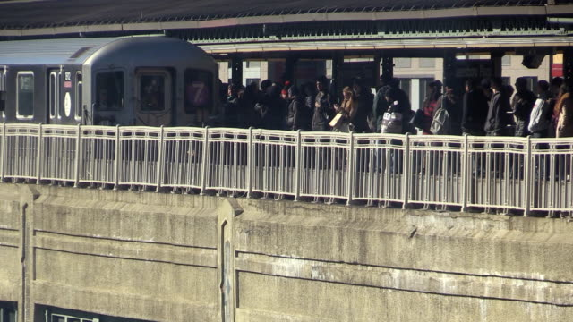 Subway 7 Train in Queensboro Plaza New York City Subway train arriving at an elevated outdoor station platform with a crowd of awaiting commuters during rush hour in Queens, New York City. subway platform stock videos & royalty-free footage