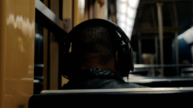 Subway commuter enjoying music during the ride Back view of unidentified black man listening to favourite music in headphones when traveling by subway. Commuting with underground headphones stock videos & royalty-free footage