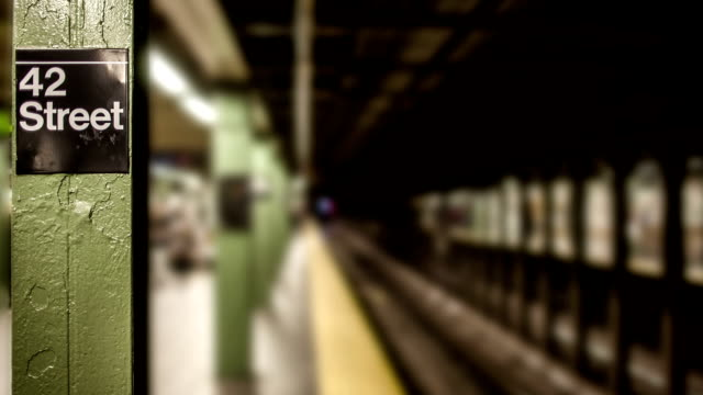 Subway Station in Major City subway train pulls into station in New York City at 42nd street station (slow camera moving in) subway station stock videos & royalty-free footage