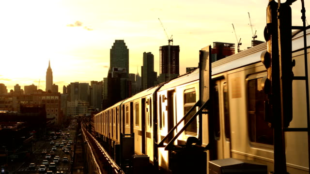 Subway Train in Queens New York City Subway train passing through Queens with the Manhattan skyline in the background during sunset in New York City. underground stock videos & royalty-free footage