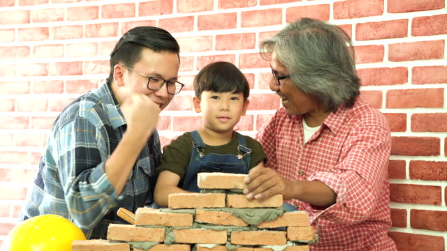 Success!! grandfather, father and son lay brick on a new house together