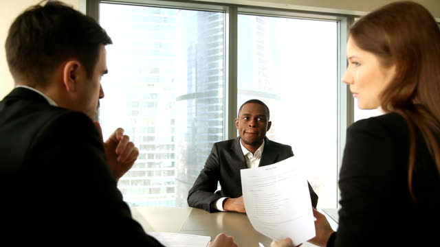 Successful african candidate hired after job interview, handshaking, signing papers video